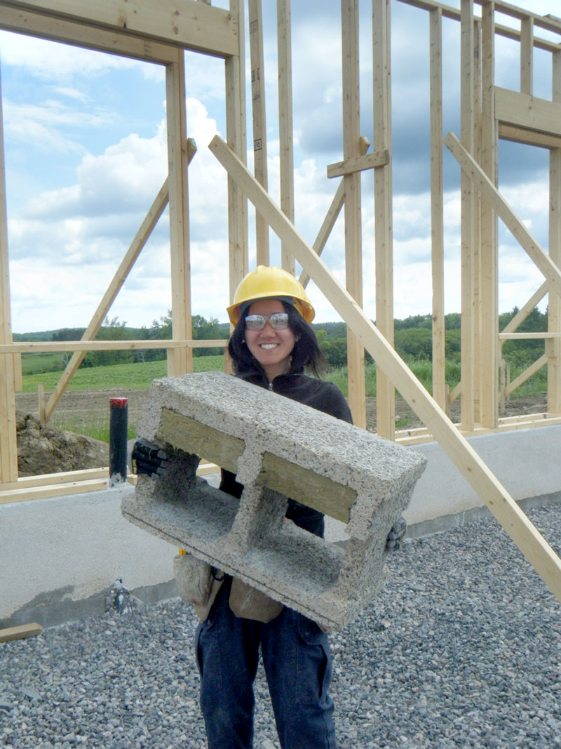 Image of young woman holding concrete brick at build site